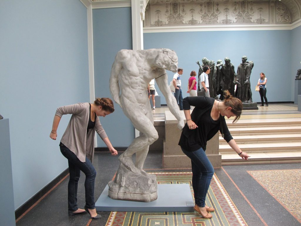 Two ladies do the Beyonce single ladies dance next to a statue doing the same pose.